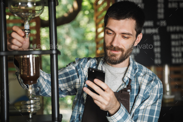 Image of joyous barista boy using cellphone and making coffee wh - Stock Photo - Images
