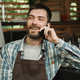 Image of happy waiter boy sitting at the bar and using cellphone - PhotoDune Item for Sale