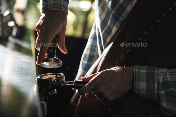Image closeup of masculine barista man making coffee while worki - Stock Photo - Images