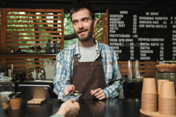 Portrait of happy barista man taking credit card from customer w - Stock Photo - Images
