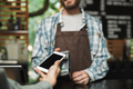 Portrait of caucasian barista man holding consumer terminal for - PhotoDune Item for Sale