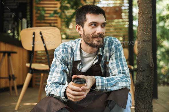 Photo of bearded waiter man sitting on wooden floor while workin - Stock Photo - Images