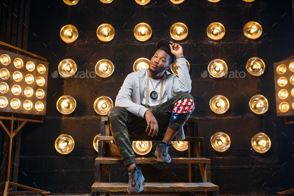 Black rapper in cap poses, perfomance on stage - Stock Photo - Images
