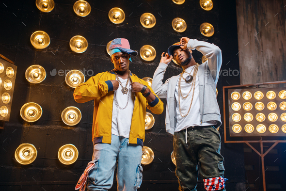 Black rappers in caps on stage with spotlights - Stock Photo - Images