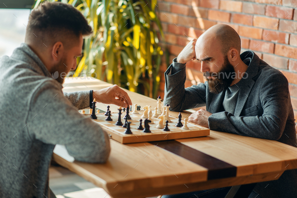 Male chess players, move the black elephant - Stock Photo - Images