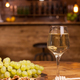 Glass of white wine with fresh grapes and wolnuts on a wooden plate in a vintage restaurant - PhotoDune Item for Sale
