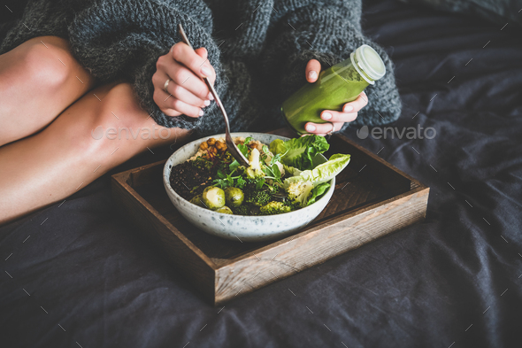 Healthy vegan bowl on tray and woman eating - Stock Photo - Images