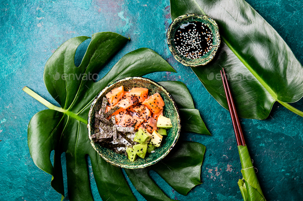 Hawaiian salmon poke poce with avocado, rice and sesamo served in bowls on tropical leaves - Stock Photo - Images