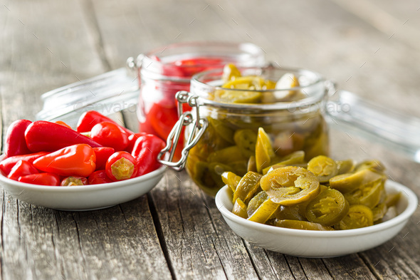 Pickled chili peppers and jalapeno peppers. - Stock Photo - Images