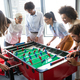 Coworkers playing table football on break from work - PhotoDune Item for Sale