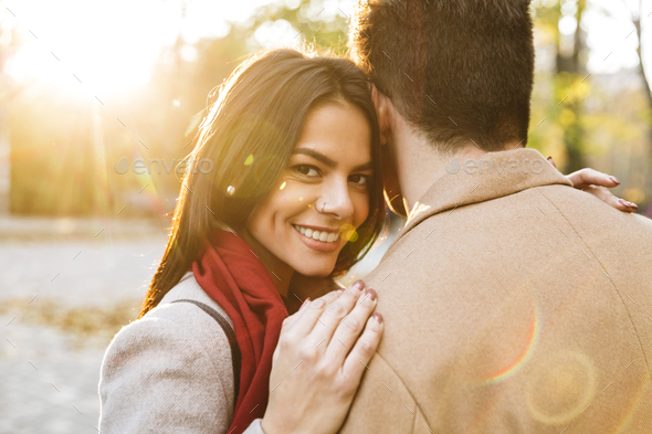 Image of young beautiful woman hugging her boyfriend and smiling in park - Stock Photo - Images