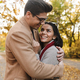 Image of charming brunette couple smiling and hugging in autumn park - PhotoDune Item for Sale