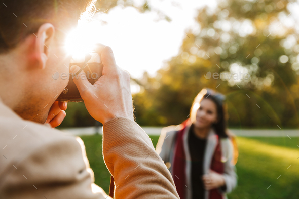 Blurry photo of young woman standing in front of boyfriend which taking photo of her - Stock Photo - Images