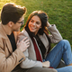 Image of brunette caucasian couple smiling and hugging while sitting on grass in park - PhotoDune Item for Sale