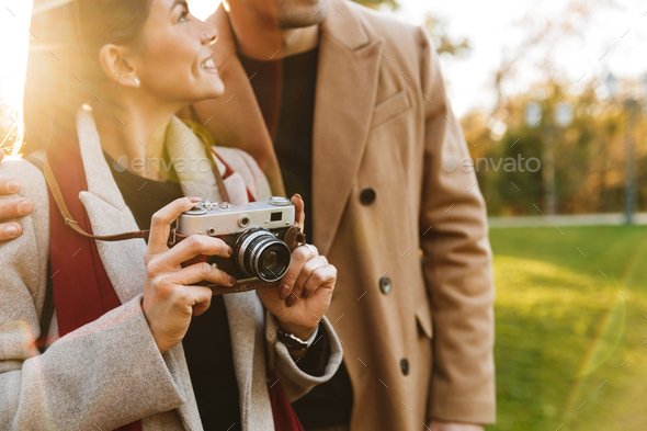 Portrait of smiling couple using vintage camera while walking in autumn park - Stock Photo - Images