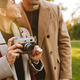 Portrait of smiling couple using vintage camera while walking in autumn park - PhotoDune Item for Sale