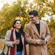 Portrait of european couple drinking takeaway coffee from paper cups while walking in autumn park - PhotoDune Item for Sale