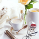 Morning coffee mug with glasses on a notebook, candle and rose on a white bed top view . Woman cozy - PhotoDune Item for Sale