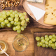 Top view of fresh grapes next to various cheeses on a wooden table - PhotoDune Item for Sale