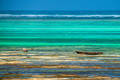 Wooden boats at low tide on beach in Zanzibar - PhotoDune Item for Sale
