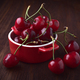 red bowl full of cherries on wood - PhotoDune Item for Sale