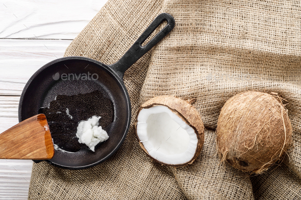 Coconut, shell with meat, cast iron skillet and spatula on hemp - Stock Photo - Images