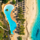 Aerial view of pool, umbrellas, sandy beach with green trees - PhotoDune Item for Sale