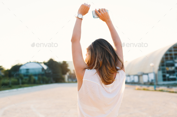 Joyful girl dancing in the street on a sunny day holding hands up - Stock Photo - Images