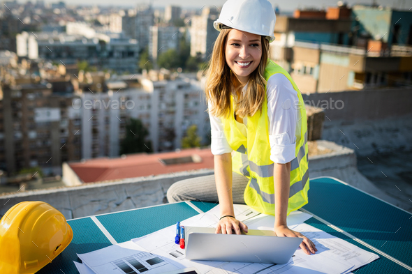 Young female construction specialist engineer reviewing blueprints at construction site - Stock Photo - Images