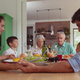 Front view of multi-generation Caucasian family praying before having food on dining table at home - PhotoDune Item for Sale