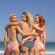 Rear view of diverse female friends with arm around looking at camera on the beach - PhotoDune Item for Sale