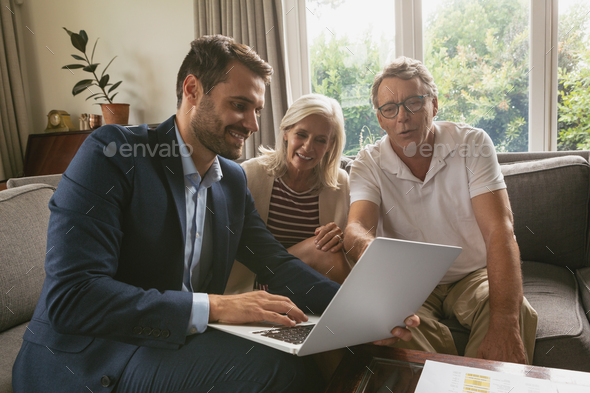 Active senior Caucasian couple discussing with real estate agent over laptop in living room at home - Stock Photo - Images