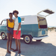 Front view of diverse couple looking at camera while standing near camper van at beach - PhotoDune Item for Sale