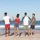 Rear view of diverse friends walking together on the beach - PhotoDune Item for Sale