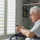 Side view of active senior Caucasian man in wheelchair using mobile phone at home - PhotoDune Item for Sale