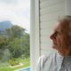 Front view of thoughtful active senior Caucasian man looking through window in a comfortable home - PhotoDune Item for Sale