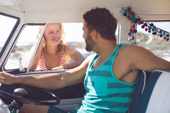 Caucasian man in camper van talking with woman while woman standing outside the van at beach - Stock Photo - Images