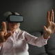 Front view of active senior Caucasian woman using virtual reality headset in living room at home - PhotoDune Item for Sale