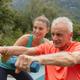 Caucasian female trainer assisting active senior Caucasian man to exercise with dumbbells - PhotoDune Item for Sale