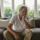 Sad active senior Caucasian man with hand on face sitting on sofa in a comfortable home - PhotoDune Item for Sale