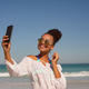 Front view of beautiful happy woman taking selfie with mobile phone at beach in the sunshine - PhotoDune Item for Sale