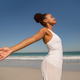 Beautiful African american woman with arms stretched out standing on beach in the sunshine - PhotoDune Item for Sale