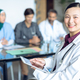 Happy Asian female doctor looking at camera while using digital tablet in the hospital.  - PhotoDune Item for Sale