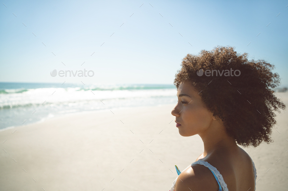Side view of thoughtful African american woman standing on the beach - Stock Photo - Images