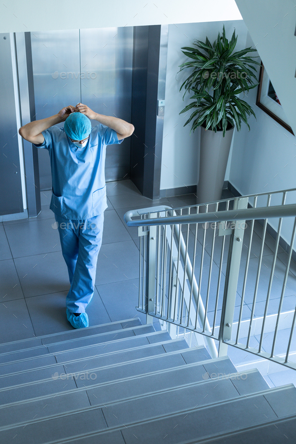 High angle view of Caucasian male surgeon wearing surgical mask while standing at stairs - Stock Photo - Images