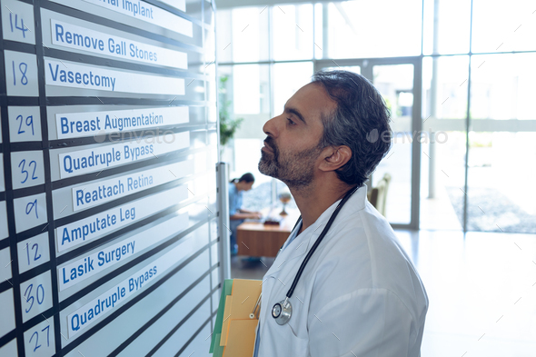 Side view of mixed-race male doctor checking his shifts on chart at hospital - Stock Photo - Images