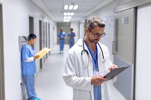 Caucasian male doctor writing on clipboard in corridor at hospital.  - Stock Photo - Images