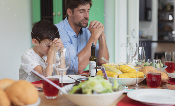 Caucasian father and son praying before having lunch at dining table - Stock Photo - Images