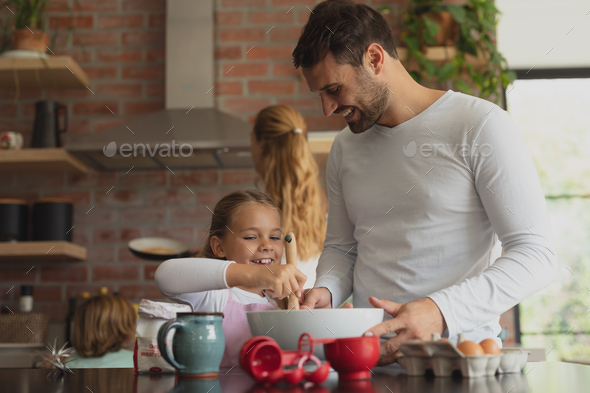 Happy Caucasian father and daughter preparing cookie on worktop in kitchen - Stock Photo - Images