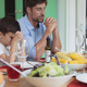 Caucasian father and son praying before having lunch at dining table - PhotoDune Item for Sale
